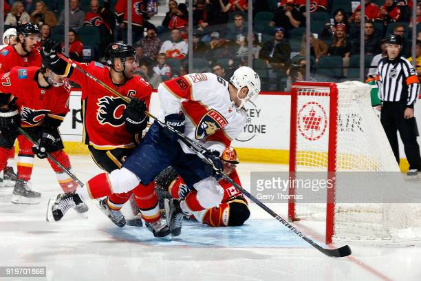 Mark Giordano of the Calgary Flames skates against Aleksander Barkov of the Florida Panthers during an NHL game on February 17 2018 at the Scotiabank...