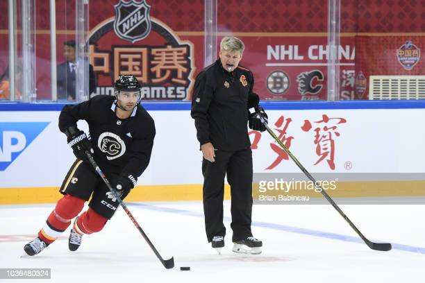 Mark Giordano of the Calgary Flames skates around head coach Bill Peters during practice at the Universiade Sports Center on September 14 2018 in...