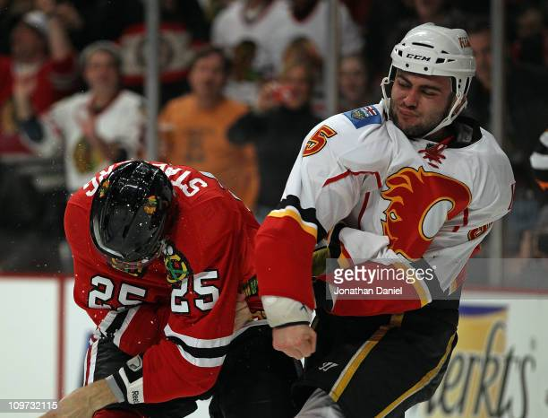 Mark Giordano of the Calgary Flames throws a punch at Viktor Stalberg of the Chicago Blackhawks in the 2nd period at the United Center on March 2...