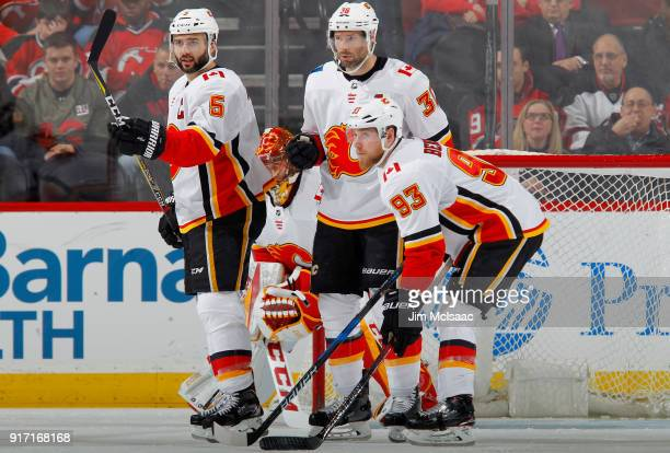 Mark Giordano Troy Brouwer and Sam Bennett of the Calgary Flames look on against the New Jersey Devils on February 8 2018 at Prudential Center in...