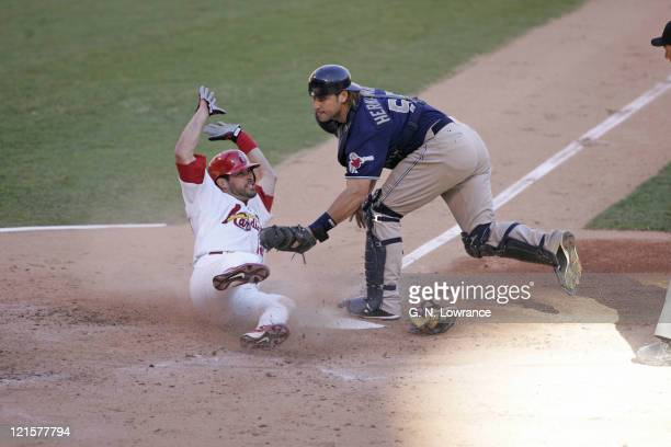 Mark Grudzielanek of the St Louis Cardinals scores ahead of the tag by Ramon Hernandez during action against the San Diego Padres during Game 2 of...