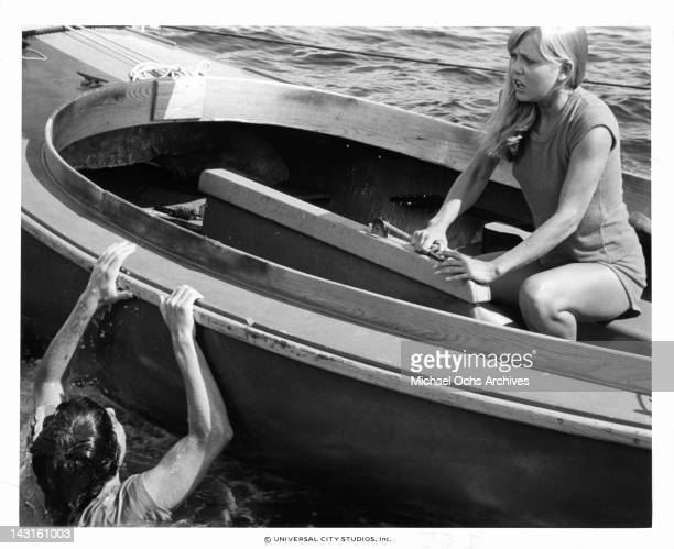 Mark Gruner swimming up to frightened Ann Dusenberry's boat in a scene from the film 'Jaws 2' 1978