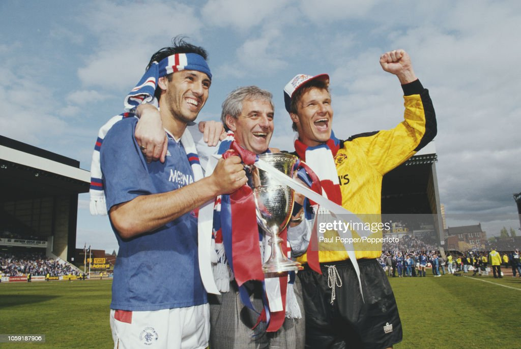 Mark Hateley (left) and Chris Woods (right) of the Rangers FC football team squad celebrate with manager Walter Smith on the pitch with the trophy after beating Aberdeen 2-0 at Ibrox Stadium in Glasgow to win the 1990-91 Scottish Premier Division championship on 11th May 1991.