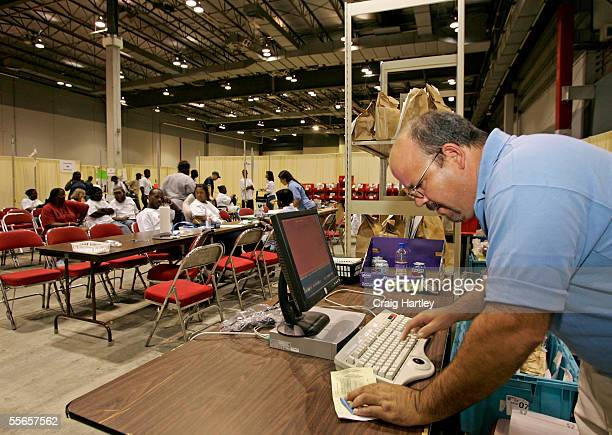 Mark Henderson uses the computer data base to check prescriptions for an evacuee as CVS Pharmacy sets up 24 hour service for evacuees from New...