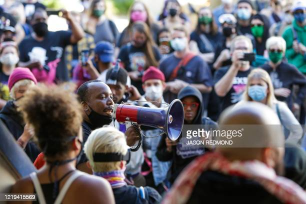 Mark Henry Jr. Of Black Lives Matter addresses a crowd in an area being called the Capitol Hill Autonomous Zone located on streets that reopened to...
