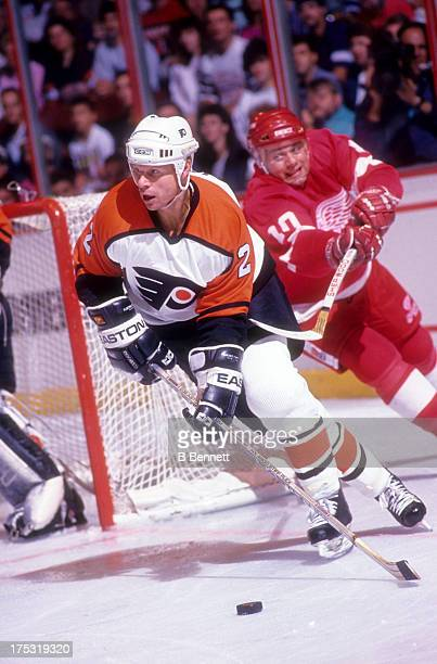 Mark Howe of the Philadelphia Flyers skates with the puck as Jimmy Carson of the Detroit Red Wings tries to hook him circa 1990 at the Spectrum in...