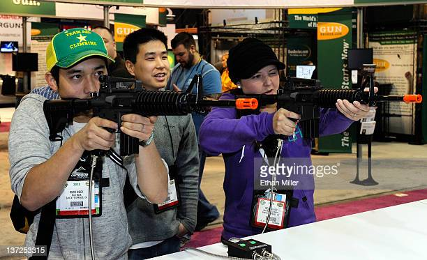 Mark Hsieh and Melissa Oaki play the Shooting Box simulation game using Airsoft M4A1 rifles as Kenny Suh looks on at the National Shooting Sports...