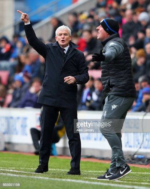 Mark Hughes manager of Southampton and Paul Cook manager of Wigan Athletic gives instructions from the touchline during The Emirates FA Cup Quarter...