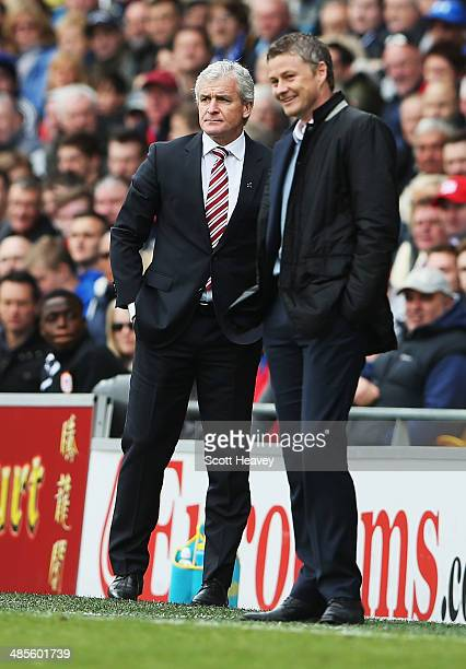 Mark Hughes manager of Stoke City and Ole Gunnar Solskjaer manager of Cardiff City look on from the touchline during the Barclays Premier League...