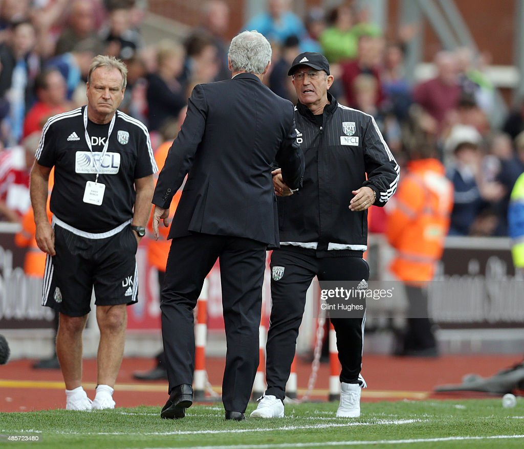 Mark Hughes (C) manager of Stoke City and Tony Pulis (R) manager of West Bromwich Albion shake hands at the end of the game during the Barclays Premier League match between Stoke City and West Bromwich Albion at Britannia Stadium on August 29, 2015 in Stoke on Trent, England.