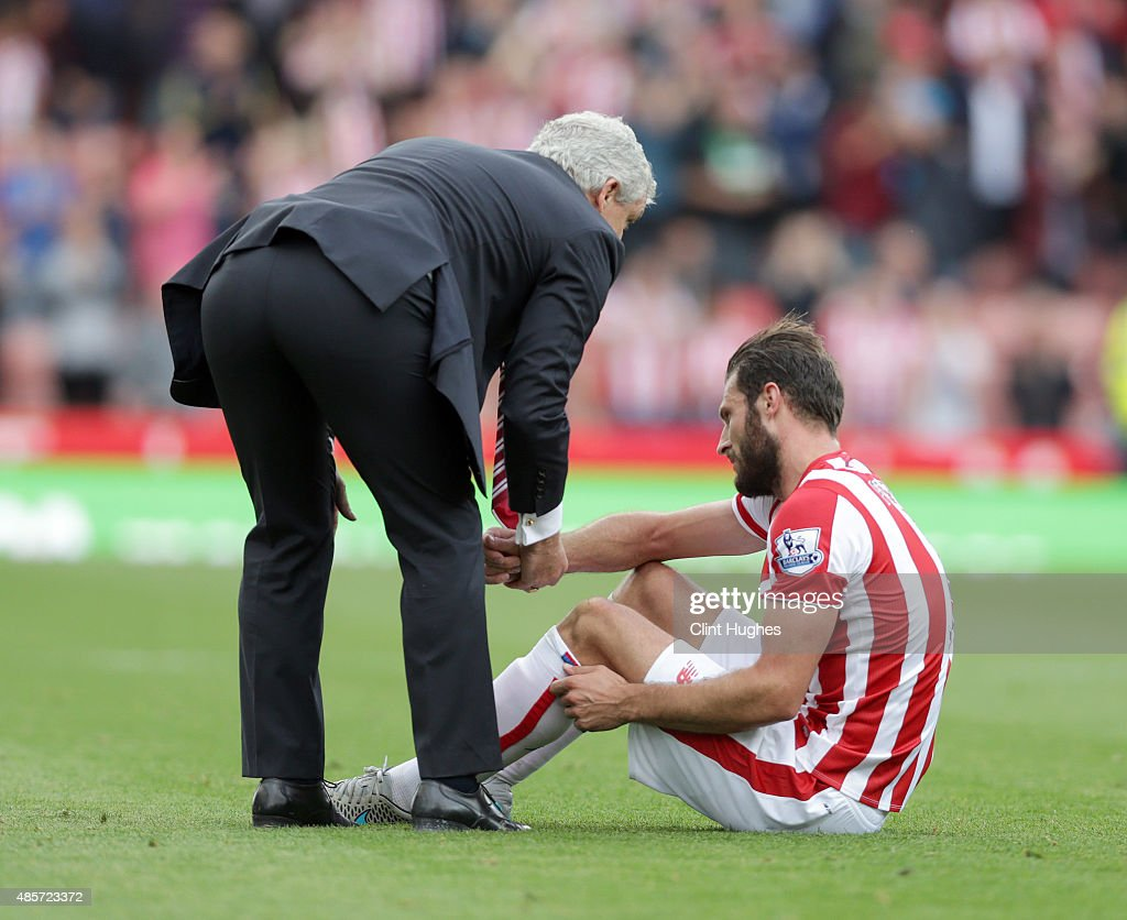 Mark Hughes (L) manager of Stoke City consoles Erik Peters after the game during the Barclays Premier League match between Stoke City and West Bromwich Albion at Britannia Stadium on August 29, 2015 in Stoke on Trent, England.