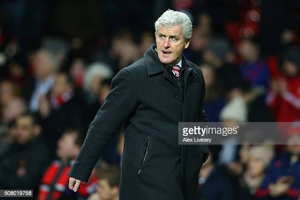 Mark Hughes manager of Stoke City leaves the pitch after the first half during the Barclays Premier League match between Manchester United and Stoke...