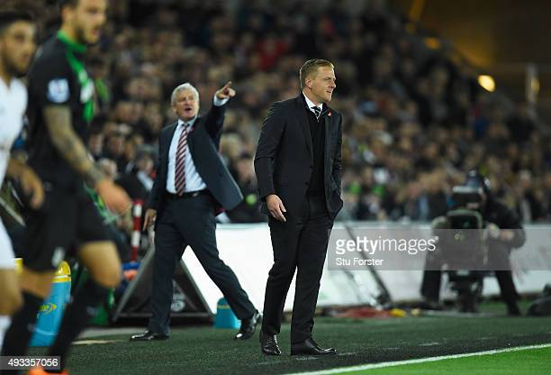 Mark Hughes manager of Stoke City points towards the scoreboard as Garry Monk manager of Swansea City looks on during the Barclays Premier League...