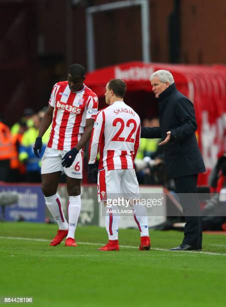 Mark Hughes Manager of Stoke City speaks to Xherdan Shaqiri of Stoke City during the Premier League match between Stoke City and Swansea City at...