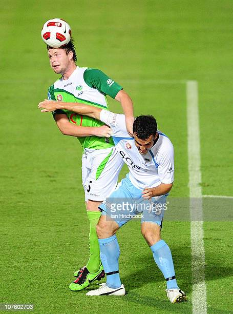 Mark Hughes of the Fury heads the ball away from Mark Bridge of Sydney during the round 18 ALeague match between the North Queensland Fury and Sydney...
