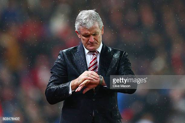 Mark Hughes the Manager of Stoke City checks his watch during the Capital One Cup semi final first leg match between Stoke City and Liverpool at the...