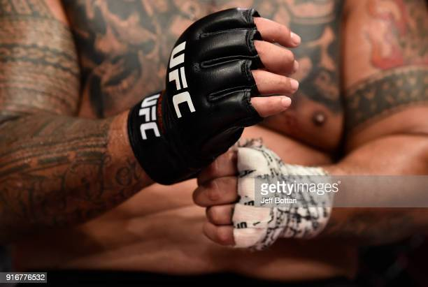 Mark Hunt of New Zealand takes off his gloves after facing Curtis Blaydes in their heavyweight bout during the UFC 221 event at Perth Arena on...