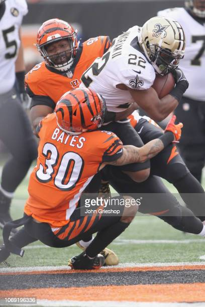 Mark Ingram II of the New Orleans Saints runs the football upfield against Jessie Bates and Adolphus Washington of the Cincinnati Bengals during...
