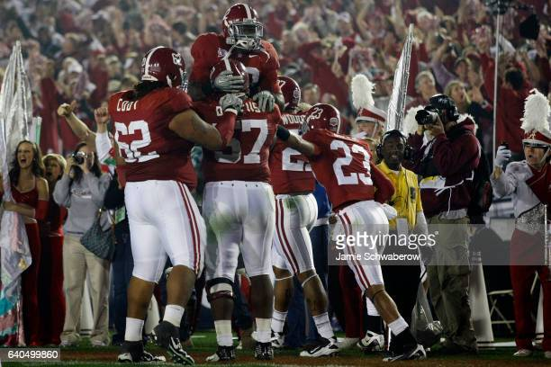 Mark Ingram jumps in the air to congratulate Marcell Dareus of the University of Alabama after his touchdown against the University of Texas during...
