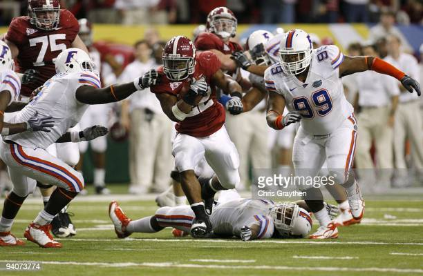 Mark Ingram of the Alabama Crimson Tide runs the ball against Omar Hunter of the Florida Gators during the SEC Championship game at Georgia Dome on...
