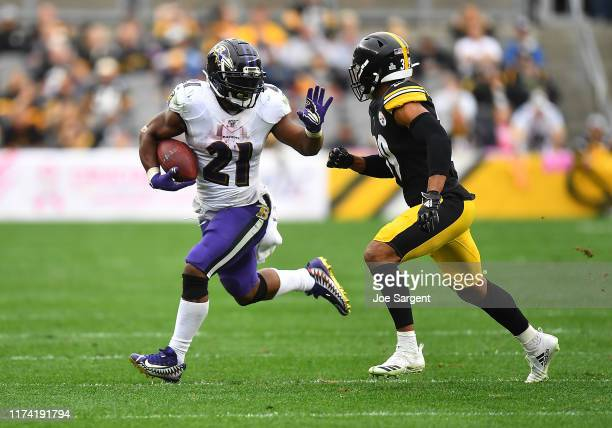 Mark Ingram of the Baltimore Ravens carries the ball in front of Minkah Fitzpatrick of the Pittsburgh Steelers during the second half at Heinz Field...
