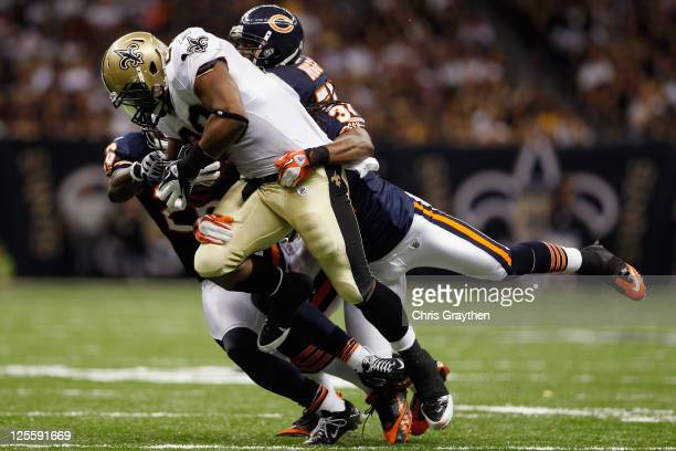 Mark Ingram of the New Orleans Saints is tackled by Brandon Meriweather of the Chicago Bears at Louisiana Superdome on September 18 2011 in New...