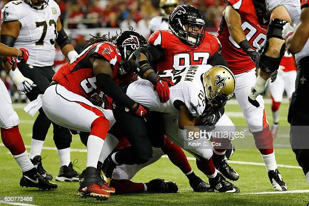 Mark Ingram of the New Orleans Saints is tackled by Grady Jarrett and De'Vondre Campbell of the Atlanta Falcons during the first half at the Georgia...