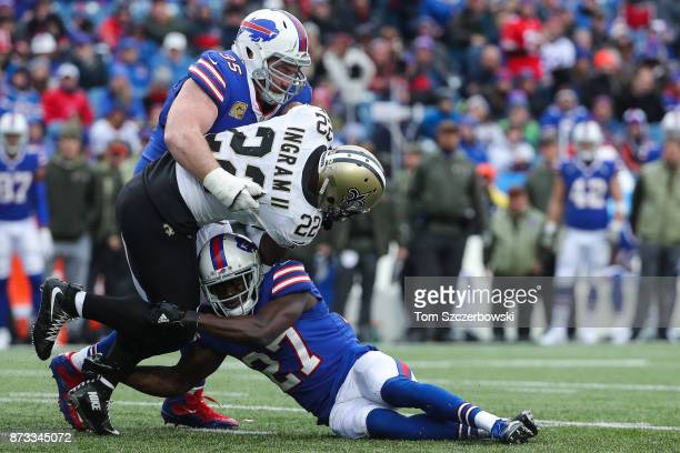 Mark Ingram of the New Orleans Saints is tackled by Kyle Williams of the Buffalo Bills and Tre'Davious White of the Buffalo Bills during the third...
