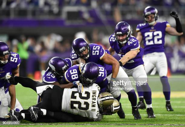 Mark Ingram of the New Orleans Saints is tackled with the ball by a group of Minnesota Vikings defenders in the first half of the NFC Divisional...