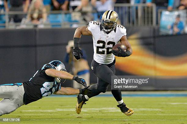 Mark Ingram of the New Orleans Saints runs past Colin Jones of the Carolina Panthers in the 1st quarter during their game at Bank of America Stadium...