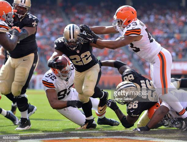 Mark Ingram of the New Orleans Saints scores a fourth quarter touchdown in front of Craig Robertson and Desmond Bryant of the Cleveland Browns at...