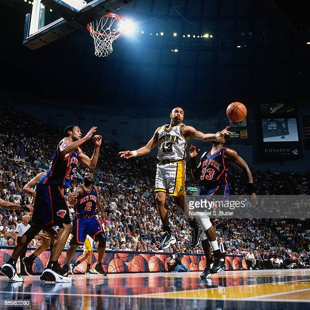 Mark Jackson of the Indiana Pacers makes a pass against Marcus Camby and Patrick Ewing of the New York Knicks in Game Two of the Eastern Conference...