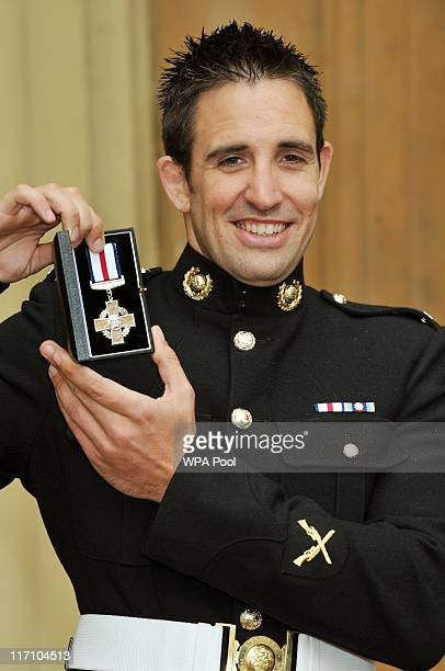 Mark Jackson of the Royal Marines holds his Conspicuous Gallantry Cross after it was presented to him by the Prince of Wales at the Investiture...