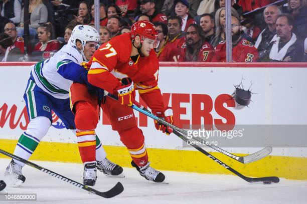 Mark Jankowski of the Calgary Flames carries the puck against Bo Horvat of the Vancouver Canucks during an NHL game at Scotiabank Saddledome on...