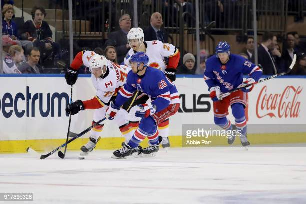 Mark Jankowski of the Calgary Flames fights for the puck against Michael Grabner of the New York Rangers in the first period during their game at...