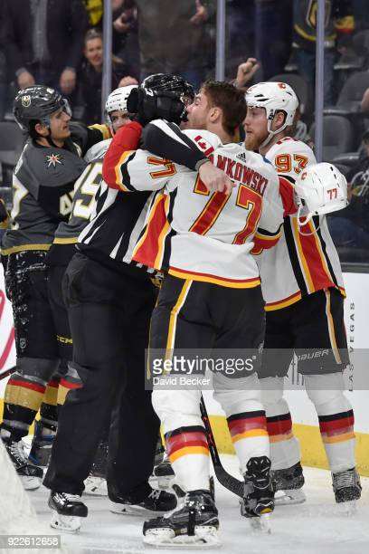 Mark Jankowski of the Calgary Flames is separated from MarcAndre Fleury of the Vegas Golden Knights by linesman Matt MacPherson during the game at...