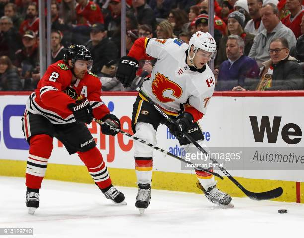 Mark Jankowski of the Calgary Flames tries to control the puck under pressure from Duncan Keith of the Chicago Blackhawks at the United Center on...