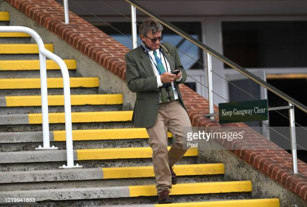 Mark Johnston checks his phone on way to winners enclosure after Tulip Fields had won the Coral Supporting Prostate Cancercouk at Goodwood Racecourse...