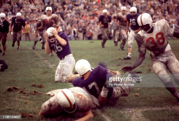 Mark Johnston of the Northwestern Wildcats gets tackled during an NCAA game against the Oklahoma Sooners on September 26, 1959 at Dyche Stadium in...