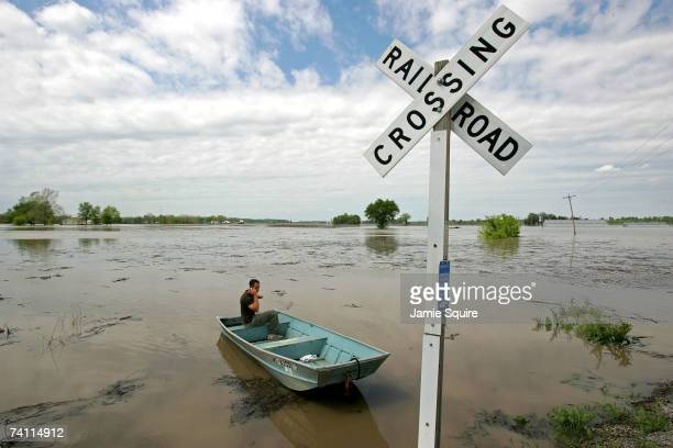 Mark Jones talks on his cell phone in his boat as he prepares to inspect the damage to his house after heavy rains caused the Missouri River to flood...