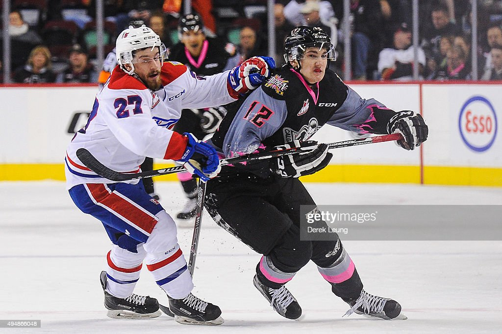 Mark Kastelic #12 of the Calgary Hitmen chases the puck against Kolten Olynek #27 of the Spokane Chiefs during a WHL game at Scotiabank Saddledome on October 29, 2015 in Calgary, Alberta, Canada.