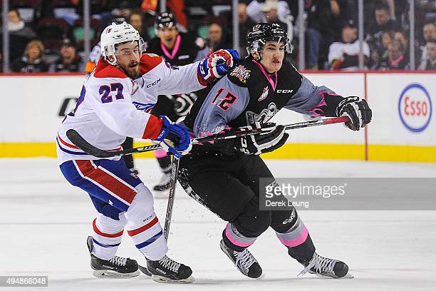 Mark Kastelic of the Calgary Hitmen chases the puck against Kolten Olynek of the Spokane Chiefs during a WHL game at Scotiabank Saddledome on October...