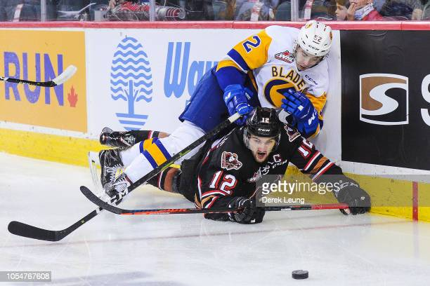 Mark Kastelic of the Calgary Hitmen gets checked by Jackson Caller of the Saskatoon Blades during a WHL game at the Scotiabank Saddledome on October...