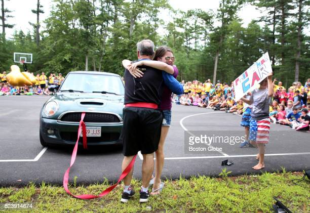 Mark Kenny of Plymouth Mass receives a hug from his daughter Katie after walking five meters on his hands while pulling a Mini Cooper at...