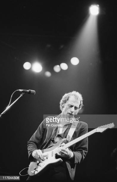 Mark Knopfler guitarist with Dire Straits playing the guitar on stage during a live concert performance by the band at Wembley Arena in London...