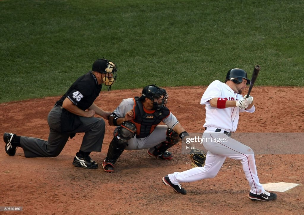 Mark Kotsay #11 of the Boston Red Sox hits a 2 RBI triple in the eighth inning as Guillermo Quiroz #24 of the Baltimore Orioles defends on September 3, 2008 at Fenway Park in Boston, Massachusetts. Umpire Jeff Nelson #45 makes the calls at home plate.