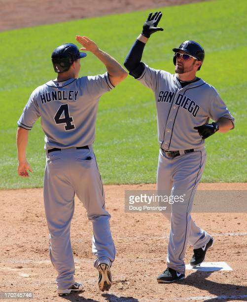 Mark Kotsay of the San Diego Padres celebrates his pinch hit two run home run off of Edgmer Escalona of the Colorado Rockies with Nick Hundley of the...