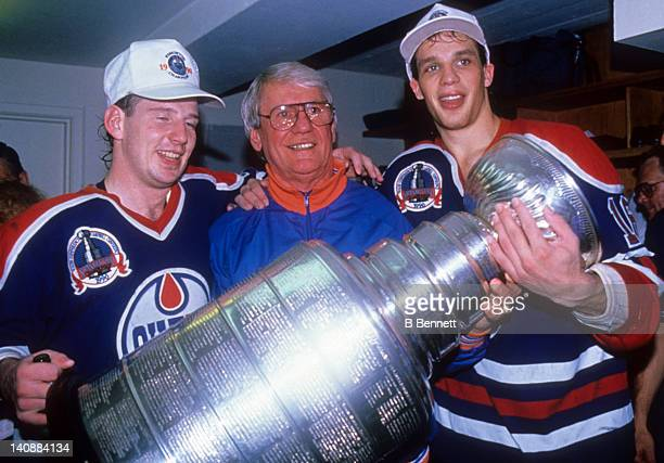 Mark Lamb, designated co-coach John Muckler and Kelly Buchberger of the Edmonton Oilers celebrate with the Stanley Cup in the locker room after the...