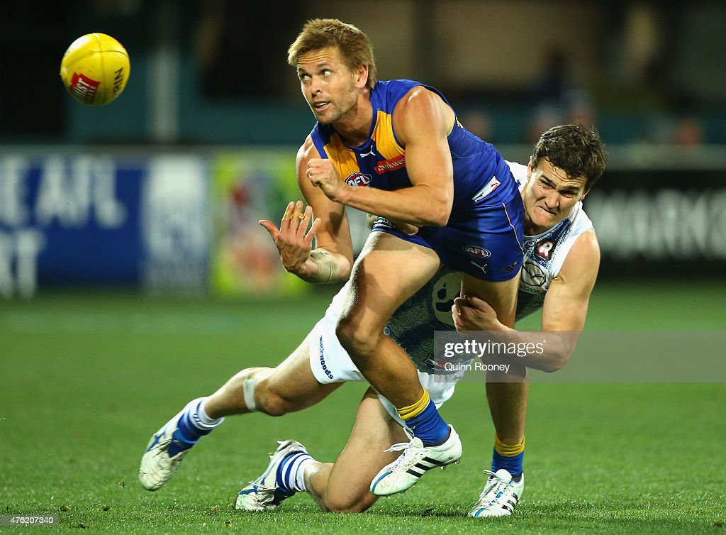 Mark LeCras of the Eagles handballs whilst being tackled by Scott Thompson of the Kangaroos during the round 10 AFL match between the North Melbourne Kangaroos and the West Coast Eagles at Blundstone Arena on June 7, 2015 in Hobart, Australia.
