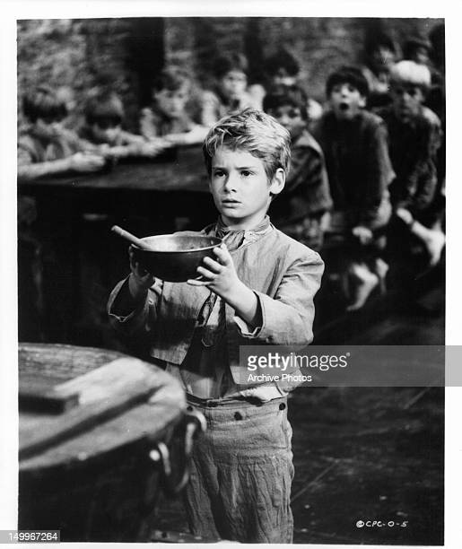 Mark Lester holding up bowl for soup in a scene from the film 'Oliver!', 1968.